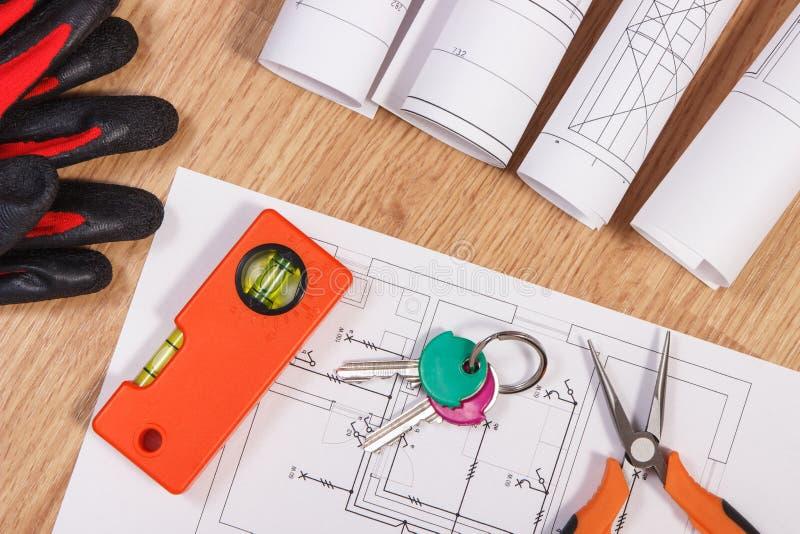 Домашние ключи с электрическими чертежами, защитными перчатками и оранжевыми инструментами работы, концепцией дома здания стоковая фотография rf