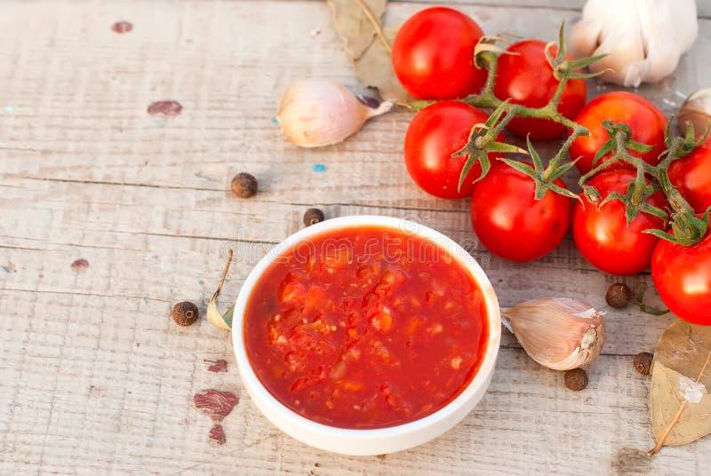 Домашние adjika, томаты вишни, чеснок и специи стоковое изображение