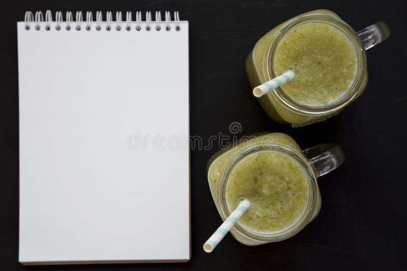 Домашний зеленый огурчик яблочный смузи в стеклянных барах, пустой блокноте на черном фоне, вид сверху Плоский слой, верхняя част стоковое фото
