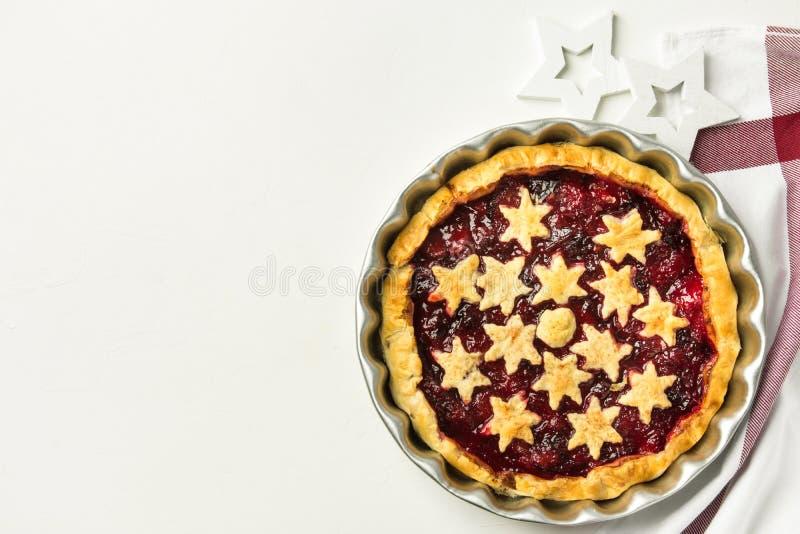 Домашний испеченный пирог рождества печенья слойки с завалкой варенья циннамона сливы украшенной со звездами Белое полотенце кухн стоковые изображения rf