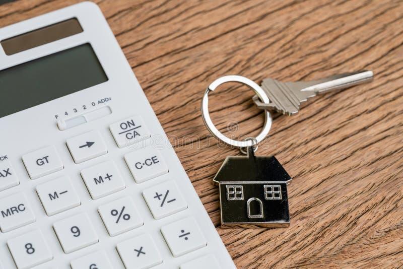 Домашний ключ с кольцом для ключей дома или keychain с белым калькулятором на деревянном столе использующ как вычисление ипотеки  стоковые фотографии rf