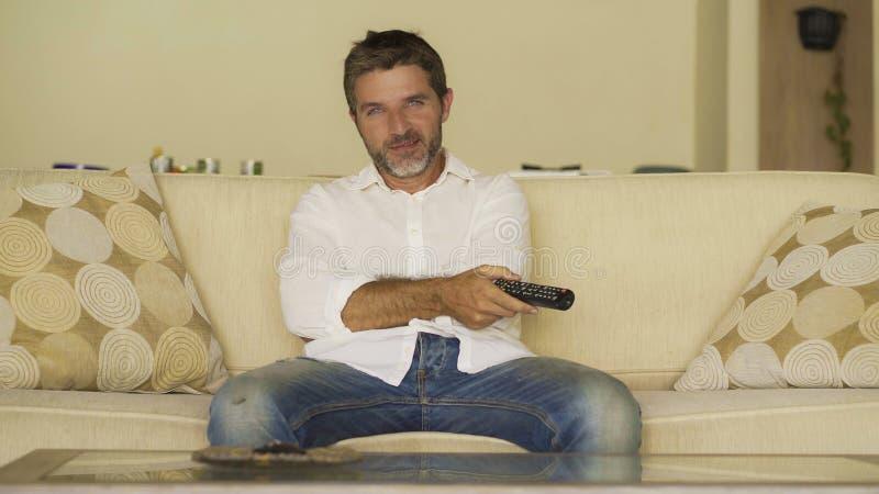 Домашний портрет образа жизни молодого привлекательного и счастливого человека смотря телепередачу или фильм держа наслаждаться р стоковое фото