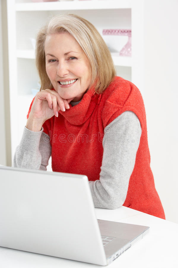 домашний старший компьтер-книжки используя женщину стоковые фотографии rf