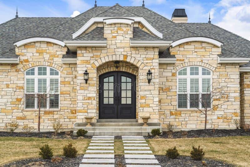 Домашний фасад с дверью кирпичной стены камня двойной стеклянной paned и сдобренными окнами стоковая фотография rf