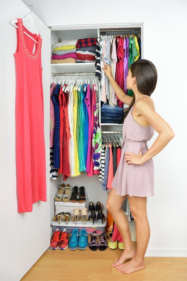 Домашний шкаф - женщина выбирая ее одежду моды стоковая фотография