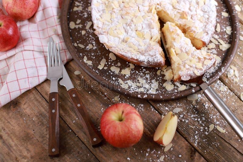 Домашний яблочный пирог - на тарелке со свежими яблоками и кориными палками на заросшем деревянном столе стоковое изображение
