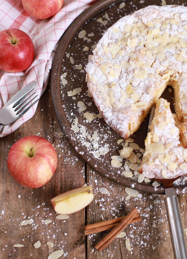 Домашний яблочный пирог - на тарелке со свежими яблоками и кориными палками на заросшем деревянном столе стоковые изображения