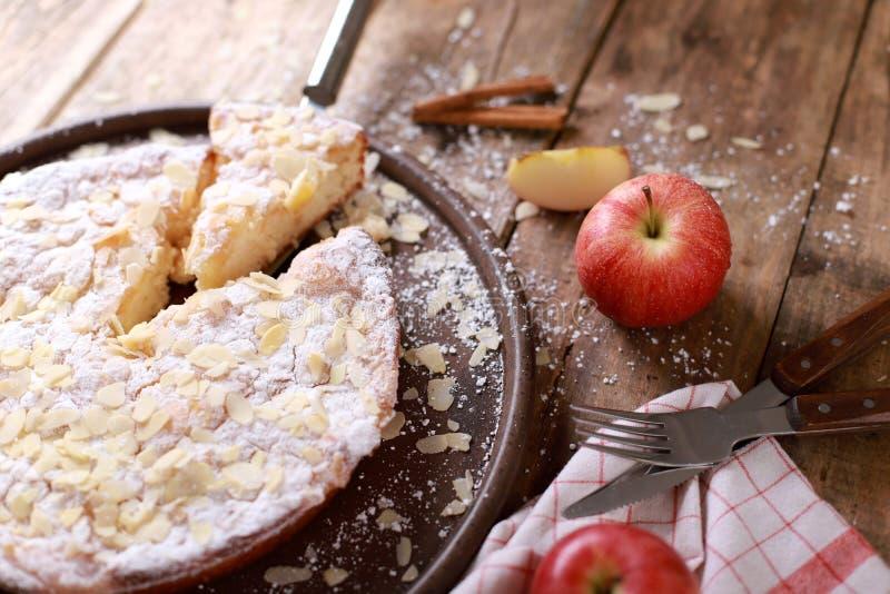 Домашний яблочный пирог - на тарелке со свежими яблоками и кориными палками на заросшем деревянном столе стоковое фото rf