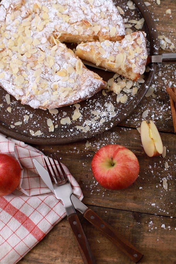 Домашний яблочный пирог - на тарелке со свежими яблоками и кориными палками на заросшем деревянном столе стоковое фото