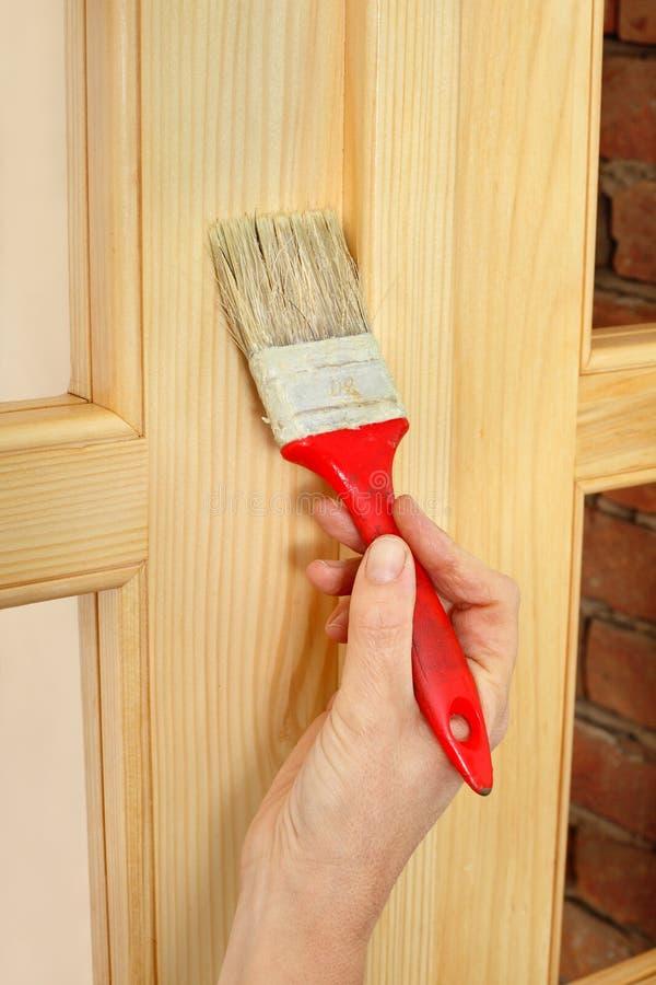 Домашняя реновация, работник крася деревянную дверь, лакируя стоковая фотография rf