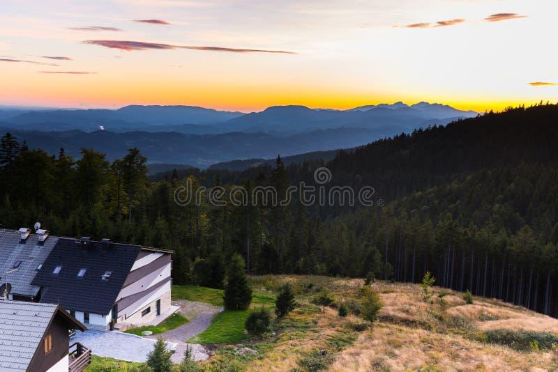 Дома горного села курорта окружили лес на заходе солнца стоковая фотография rf