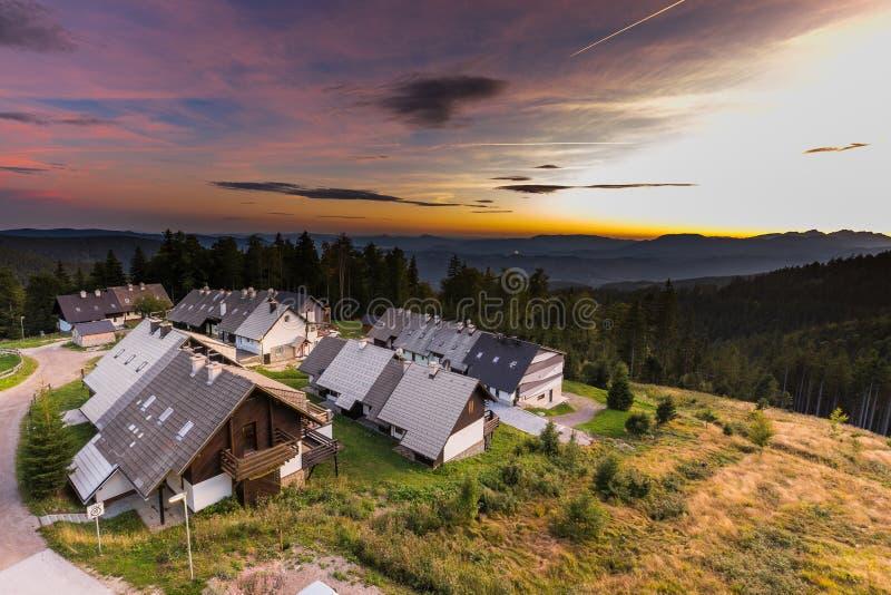 Дома горного села курорта окружили лес на заходе солнца стоковые изображения