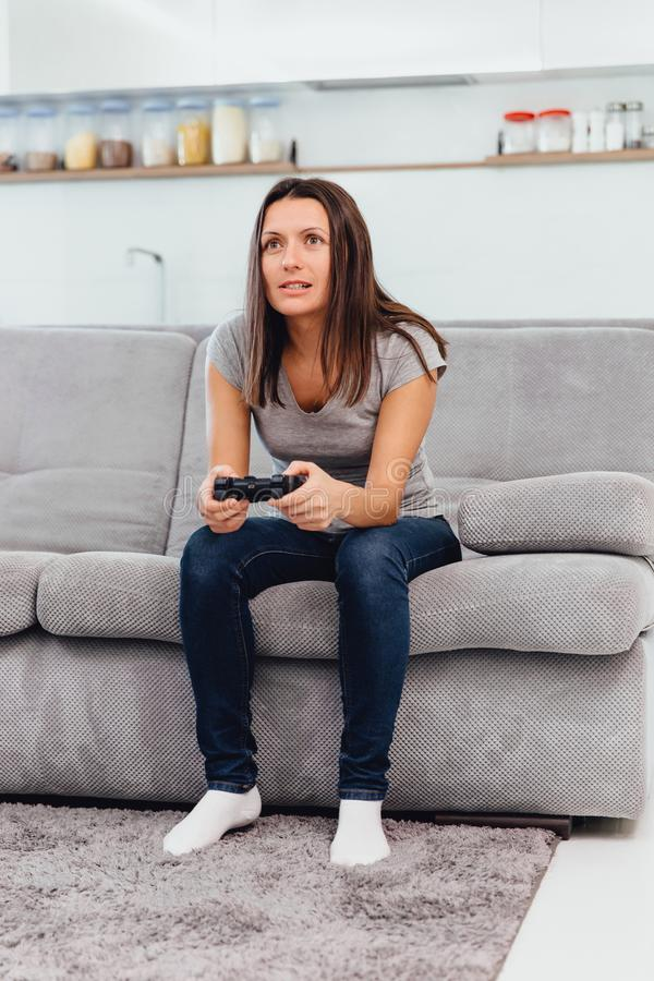 Дома, девушка играет игру на кресле стоковое фото rf