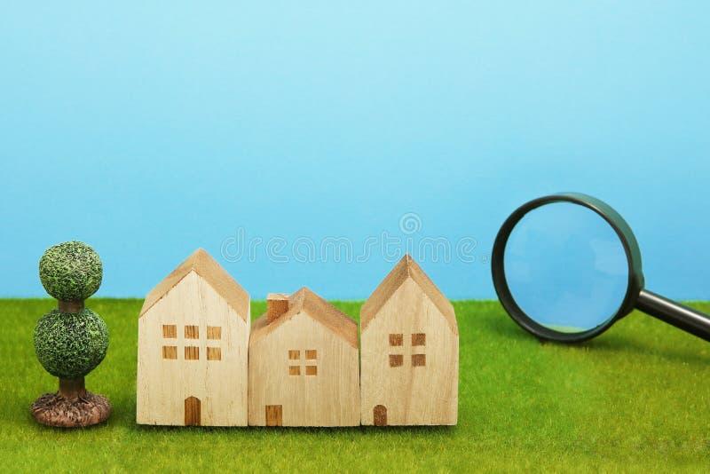 Дома и лупа на зеленой траве стоковые фотографии rf