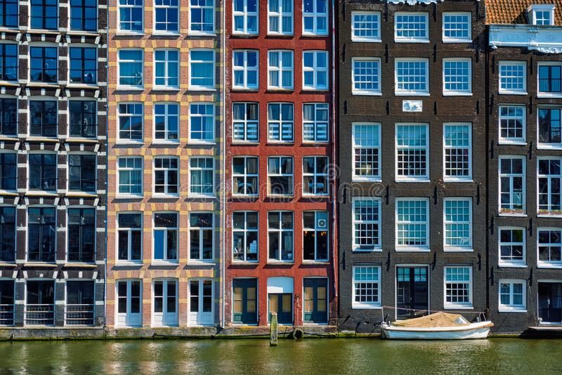 дома и шлюпка на канале Damrak Амстердама с отражением _ стоковая фотография rf