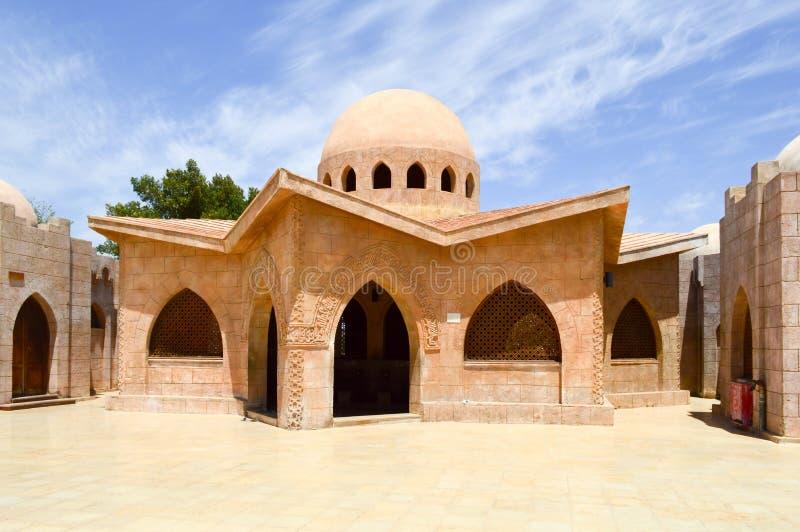 Дома малой красивой аккуратной каменной глины арабские исламские мусульманские с круглыми куполами в пустыне с пальмами в tropica стоковая фотография rf