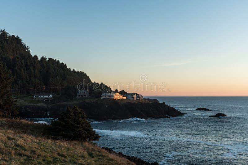 Дома на краю скалы на заходе солнца в бухте Тихого океана на побережье Орегона, США стоковое фото