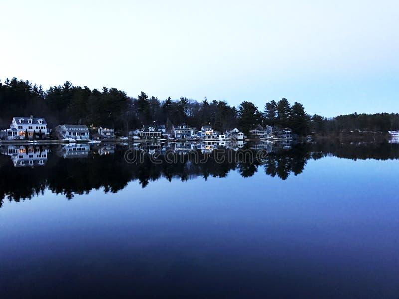 Дома озера на неподвижном голубом озере стоковое изображение rf