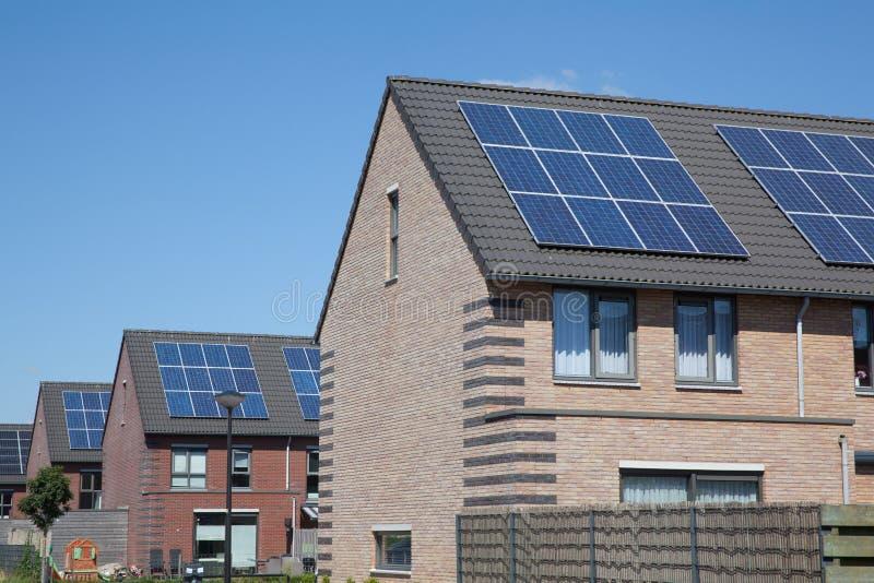 Дома с панелями солнечных батарей на крыше для альтернативной энергии стоковые изображения rf
