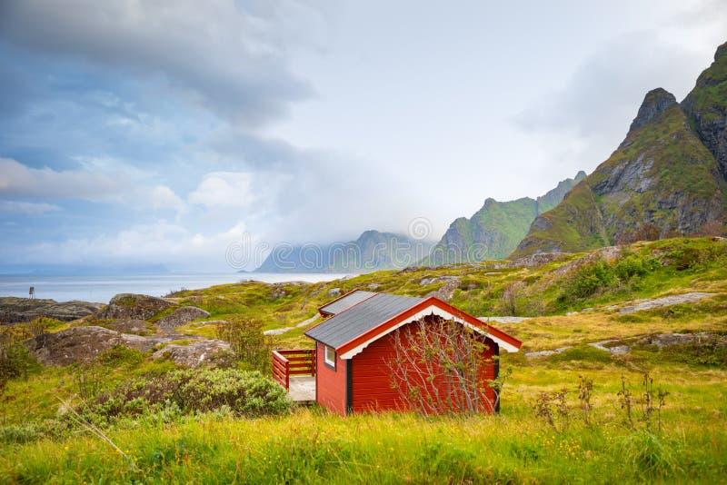 Дома традиционного красного цвета располагаясь лагерем с красивым видом на море рядом с деревней a внутри lofoten, Норвегия стоковые фотографии rf