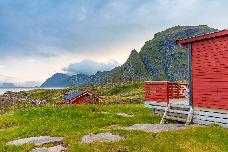 Дома традиционного красного цвета располагаясь лагерем с красивым видом на море рядом с деревней a внутри lofoten, Норвегия стоковые фото