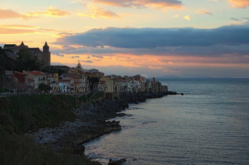 Дома Cefalu деревни на скалах и волнах разбивая утесы на заходе солнца Италия Сицилия стоковая фотография