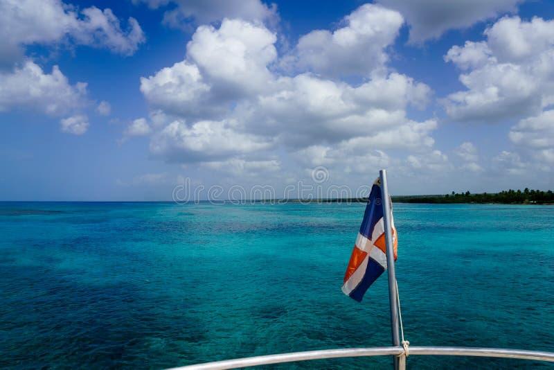 Доминиканский флаг над океаном стоковая фотография