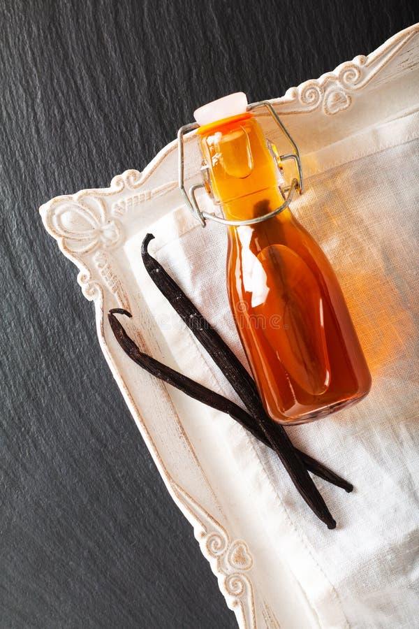 Домодельная ванильная выдержка в стеклянной бутылке и ванильных фасолях на черной предпосылке с космосом экземпляра стоковое изображение rf