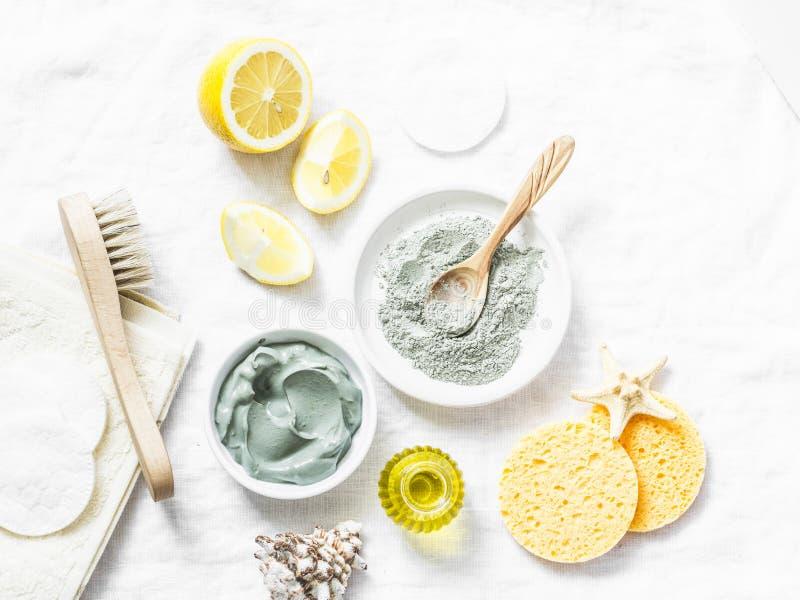 Домодельная маска ухода за лицом красоты Глина, лимон, масло, лицевая щетка - ингридиенты продуктов красоты на светлой предпосылк стоковое фото rf