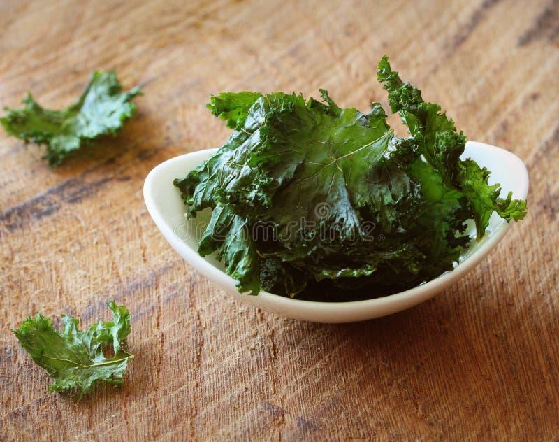 Домодельная органическая зеленая листовая капуста откалывает с солью и маслом стоковые фото