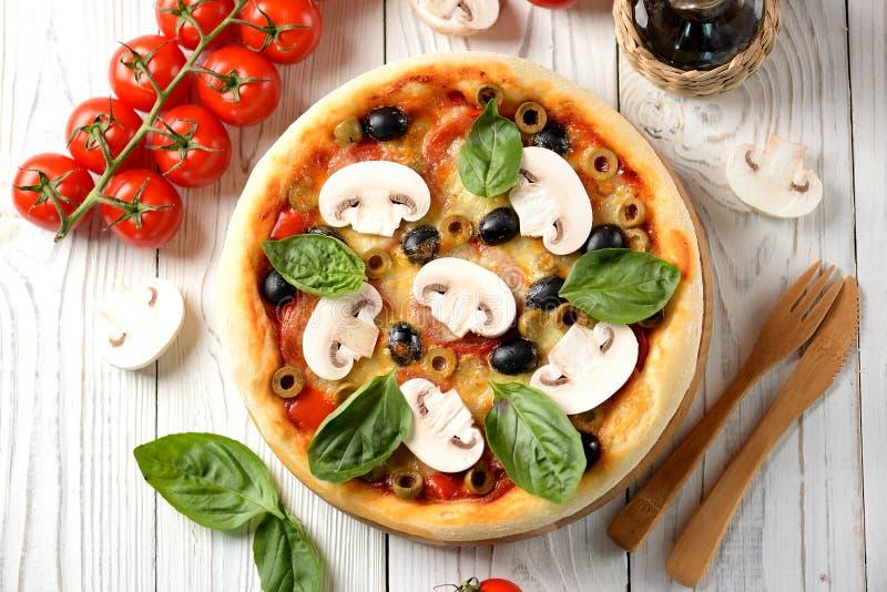 Домодельная пицца с оливками, томатами, сыром, грибами и базиликом с томатным соусом стоковое изображение