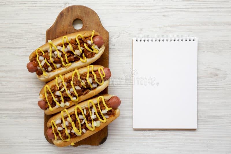 Домодельная собака chili на деревенской деревянной доске, пустой блокнот стиля detroit на белой деревянной предпосылке, взгляд св стоковое фото
