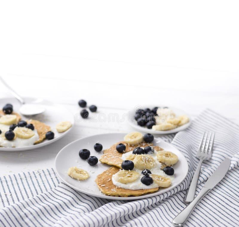 Домодельные блинчики овсяной каши с йогуртом, свежей голубикой и бананом на белой деревянной предпосылке стоковое фото rf