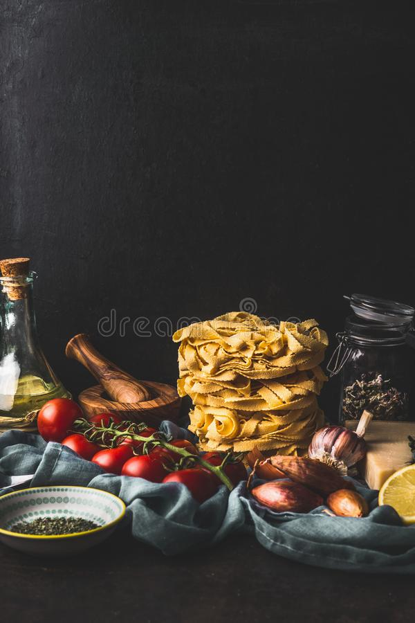 Домодельные итальянские макаронные изделия с варить ингредиенты на темном деревенском кухонном столе на предпосылке стены r E стоковые фотографии rf