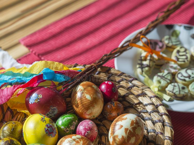Домодельные красочные покрашенные пасхальные яйца в корзине соломы плоских, печеньях пасхи и Pomlazka - чехословакском традиционн стоковая фотография rf