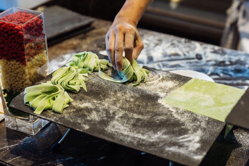 Домодельные кучи свежих макаронных изделий fettuccine шпината которые пудря муку для того чтобы держать их от вставлять стоковое изображение