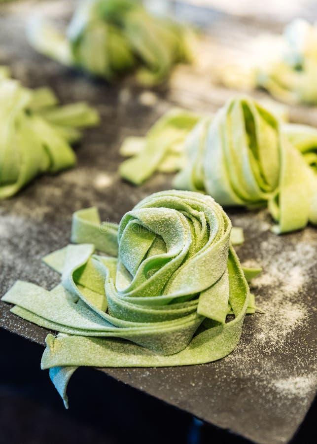 Домодельные кучи свежих макаронных изделий fettuccine шпината которые пудря муку для того чтобы держать их от вставлять стоковое фото