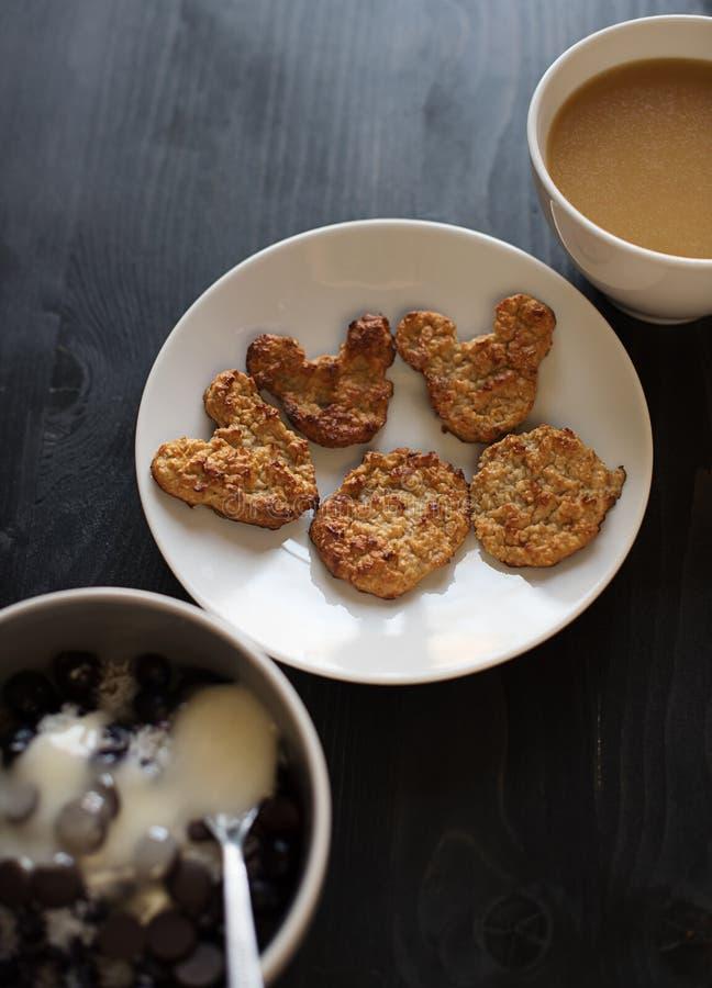 Домодельные печенья овсяной каши в центре рамки, чашки кофе и десерта на таблице в черном дереве, закуске, здоровом завтраке стоковая фотография rf