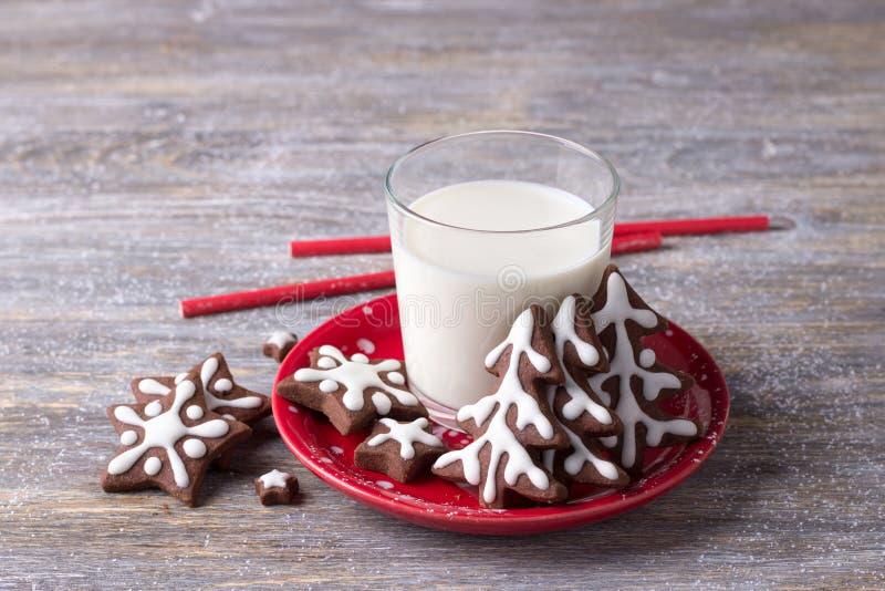 Домодельные печенья шоколада рождества, украшенные с замороженностью, со стеклом молока на деревянном столе стоковое фото