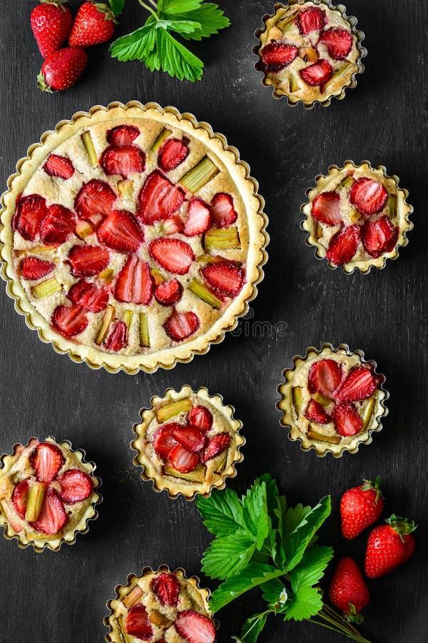 Домодельные пироги с клубникой и ревенем на черной деревянной предпосылке r r стоковые изображения