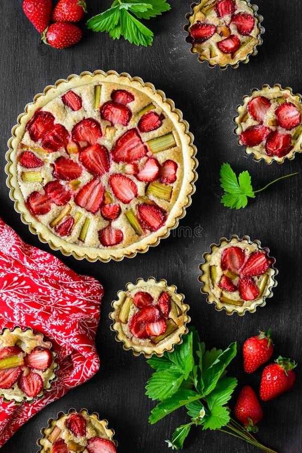 Домодельные пироги с клубникой и ревенем на черной деревянной предпосылке r r стоковая фотография