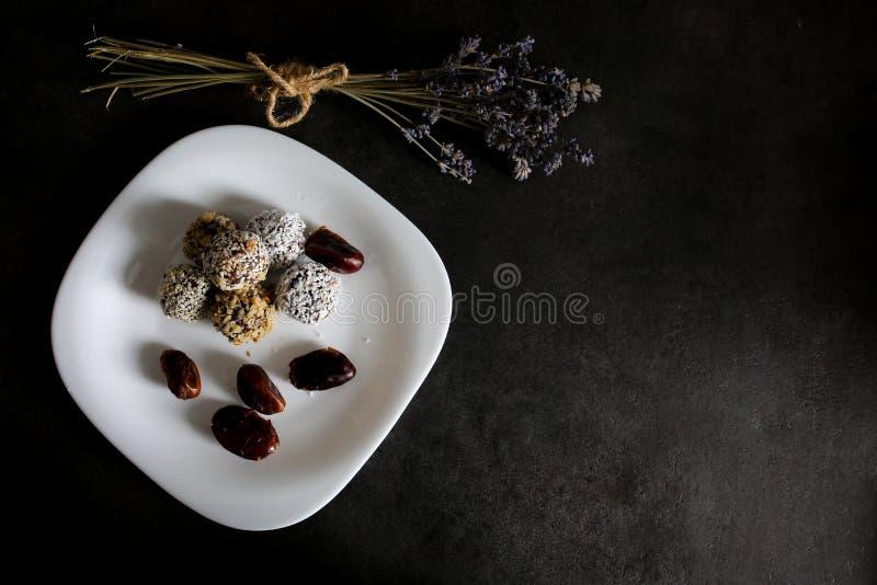 Домодельные сырцовые трюфеля с какао, гайками, кокосом и датами на белой плите и серой таблице Лаванда на предпосылке Vegan, орга стоковое фото