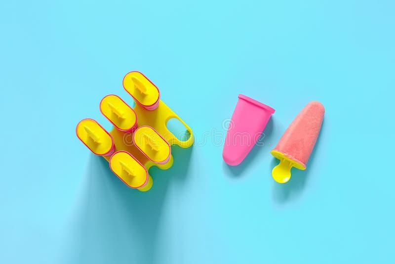 Домодельные popsicles Естественное мороженое клубники в ярких пластиковых прессформах на голубой предпосылке с космосом экземпляр стоковые изображения