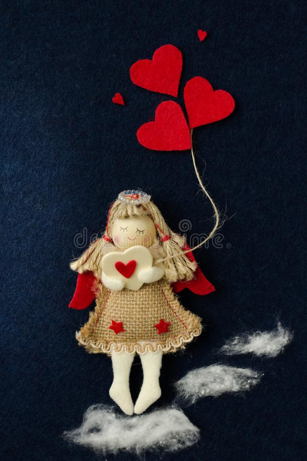 Домодельный ангел девушки игрушки держа красные сердца в ее руках и идя на тучные облака против темной предпосылки стоковые изображения rf
