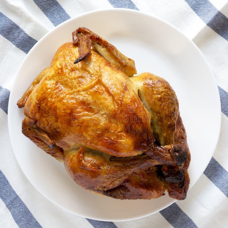 Домодельный вкусный цыпленок rotisserie на белой плите, надземном взгляде Плоское положение, сверху, взгляд сверху стоковая фотография