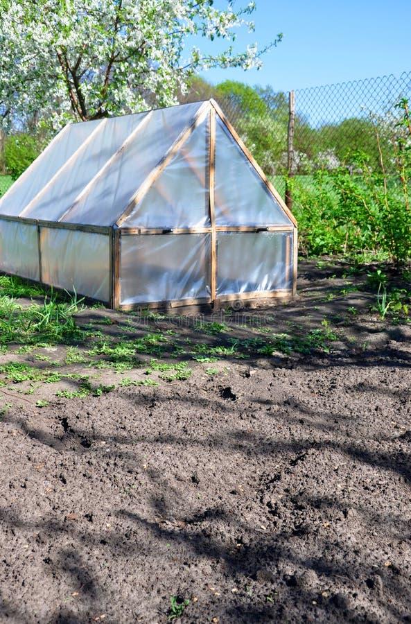 Домодельный малый парник на предпосылке вегетации весны стоковые фото