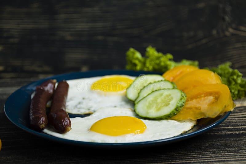 Домодельный очень вкусный завтрак с солнечной стороной вверх по яичнице, сосиске, томатам во взгляде сверху стоковое изображение
