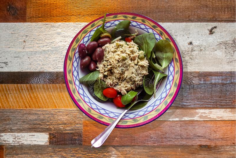 Домодельный салат из курицы служил в милом шаре с оливками kalamata шпината и томатами вишни - на грубой деревянной таблице стоковые изображения rf
