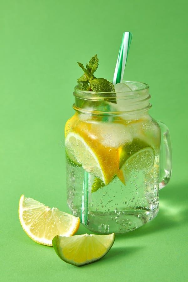Домодельный сверкная лимонад с льдом, куски известки и лимон, лист мяты с пластичными соломами в опарнике каменщика на a стоковая фотография rf