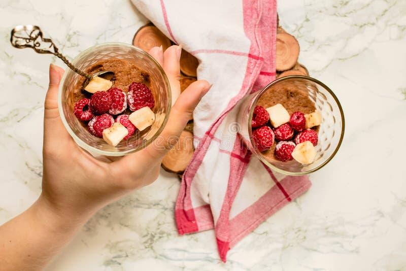 Домодельный темный мусс шоколада с бананом и ягодами Концепция еды вытрезвителя диеты Процесс еды В руках молодой стоковая фотография
